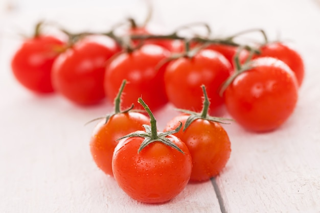 Fresh cherry tomatoes on a white surface