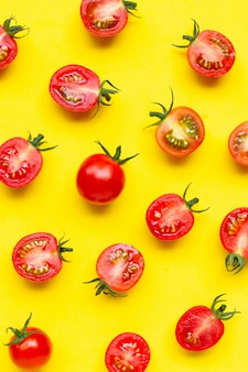 Fresh cherry tomatoes, whole and half cut isolated on yellow background.