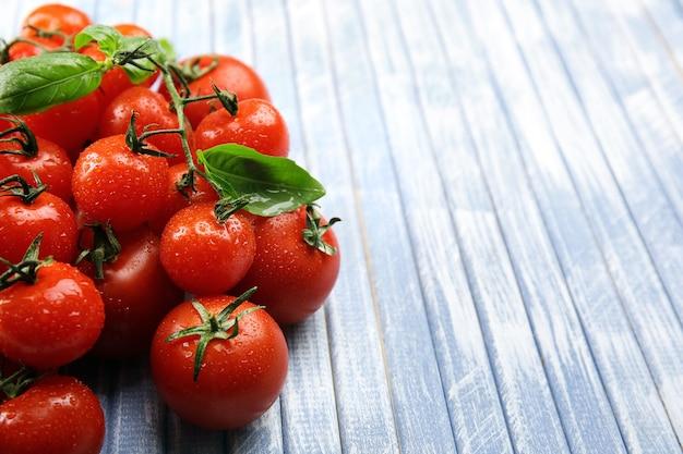 나무 테이블에 바 질 신선한 체리 토마토를 닫습니다.