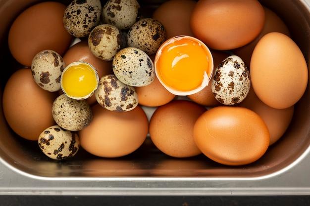 Свежие куриные и перепелиные яйца в жестяной лоток. натюрморт. вид сверху. пищевая фотография для интерьера