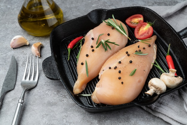 Fresh chicken breast and seasoning in the frying pan