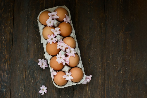 Fresh chicken brown eggs in carton box on wooden table. organic farming concept. natural healthy food.