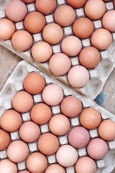 Fresh chicken brown eggs in packing on a timber floor