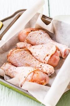 Fresh chicken drumsticks on plate