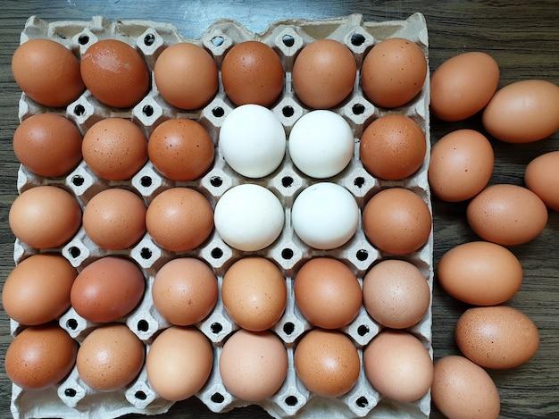 木製の背景のパッケージに新鮮な鶏卵とアヒルの卵