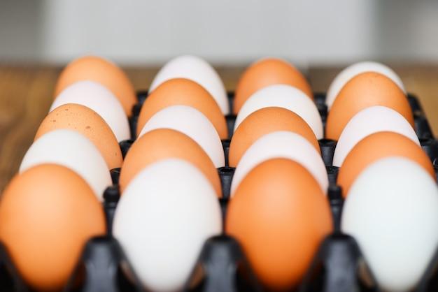 木製のテーブルのボックスに新鮮な鶏卵とアヒルの卵