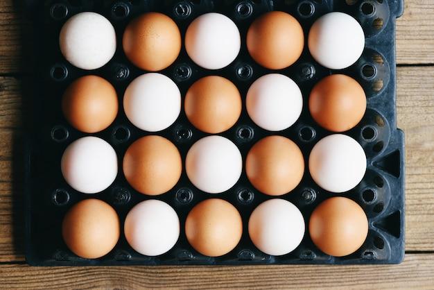 Свежие куриные яйца и утиные яйца в коробке для яиц на фоне деревянного стола, концепция света и тени