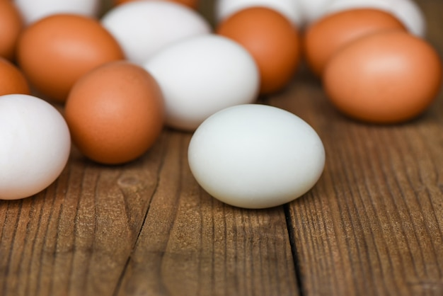 Свежие куриные яйца и утиные яйца на деревянном столе / белое и коричневое яйцо