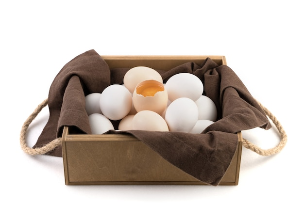 Свежие куриные яйца белые и коричневые, с разбитым яйцом в центре, где виден свежий желток.