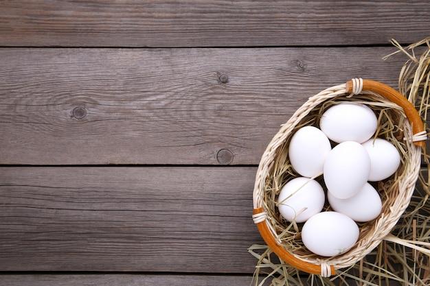 Fresh chicken eggs in basket on grey background