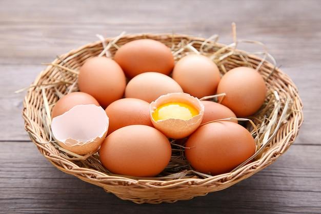 Fresh chicken eggs in basket on grey wooden background