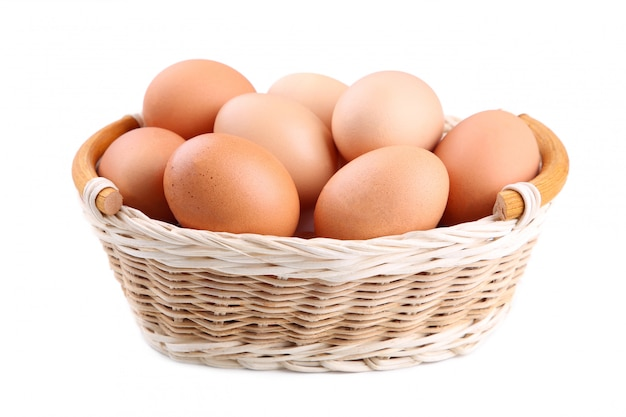 Fresh chicken eggs in basket isolated on white, close up