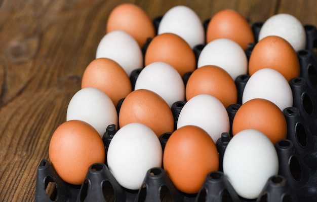 Fresh chicken eggs and duck eggs in box on wooden table