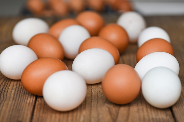 Fresh chicken eggs and duck eggs on wooden table / white and brown egg