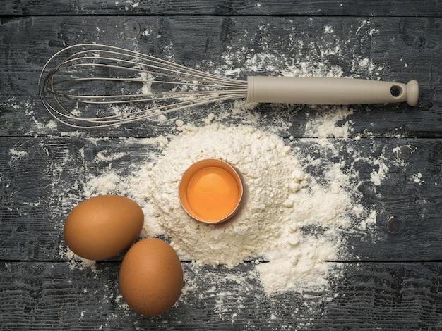 新鮮な鶏の卵、小麦粉、泡だて器で木の表面を泡立てます。天然物および厨房機器。