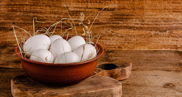 Fresh chicken eggs on hay on wooden background