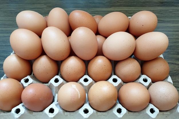 木製の背景のパッケージに新鮮な鶏卵