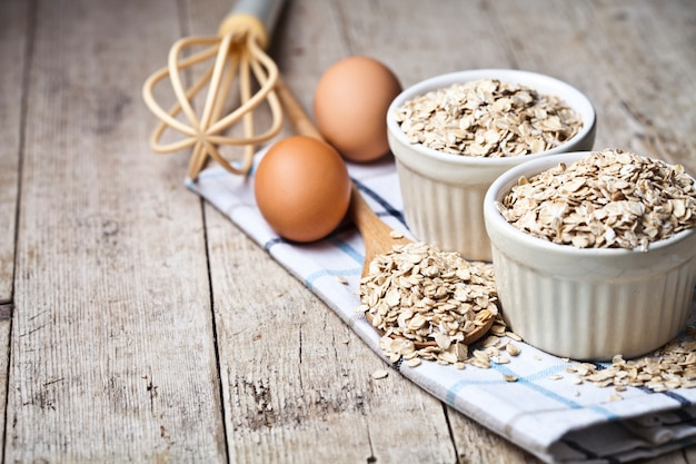 Fresh chicken eggs, oat flakes in ceramic bowls and wooden spoon