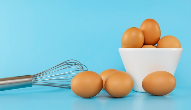 Fresh chicken eggs in white bowl and chicken eggs on blue