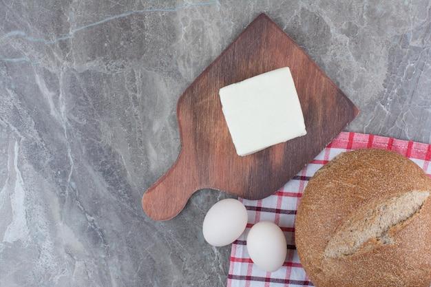 Uova di gallina fresche con pane sulla tovaglia. foto di alta qualità