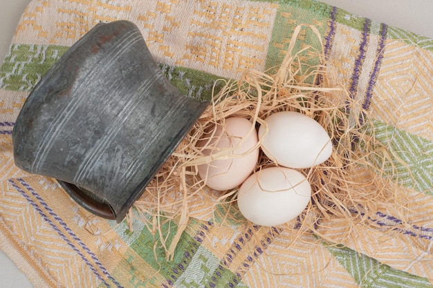 Свежие куриные яйца с сеном в древней чашке на скатерти.
