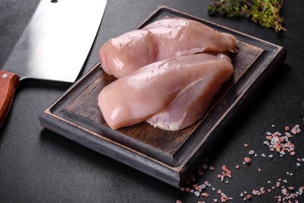 スパイスとハーブと暗いコンクリートのテーブルの上の新鮮な鶏の切り身。肉料理の準備