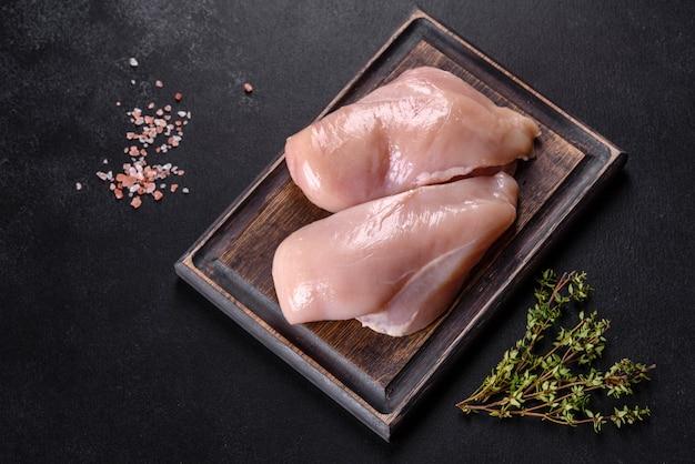 Свежее куриное филе на темном бетонном столе со специями и зеленью. подготовка к приготовлению мясных блюд