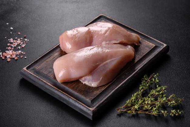 スパイスとハーブが入った暗いコンクリートのテーブルの上の新鮮な鶏ササミ。肉料理の準備