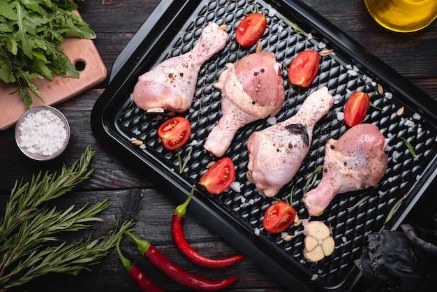 デリカテッセンからの新鮮な鶏肉、バーベキューの準備、マリネの生の鶏肉の脚が焙煎鍋にあります