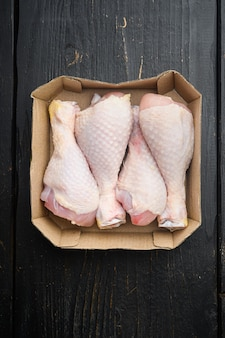 Fresh chicken leg set, in paper pack, on black wooden table table, top view flat lay