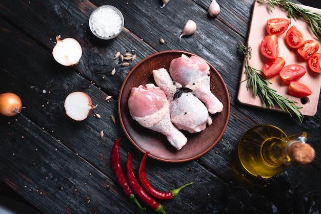 新鮮な鶏の脚を皿に盛り、焼き肉、香辛料、ハーブをテーブルに並べます