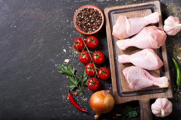 Свежие куриные ножки на деревянной доске с ингредиентами для приготовления пищи, вид сверху