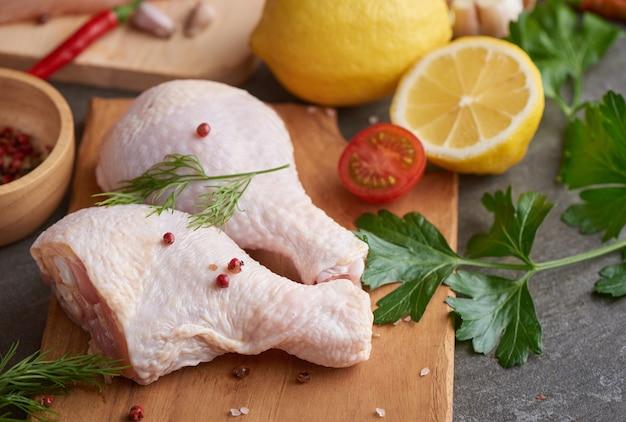 신선한 양념을 곁들인 요리와 바베큐를위한 신선한 닭고기 부분. 커팅 보드에 생 쌀된 닭 다리입니다.