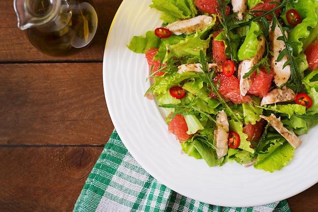 Салат из свежей курицы, грейпфрута, салата и медово-горчичной заправки. диетическое меню. правильное питание. вид сверху
