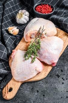 커팅 보드, 유기농 고기에 피부와 신선한 닭 허벅지. 검정색 배경.