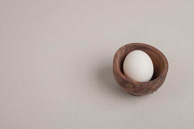 Свежее куриное белое яйцо в деревянной миске.