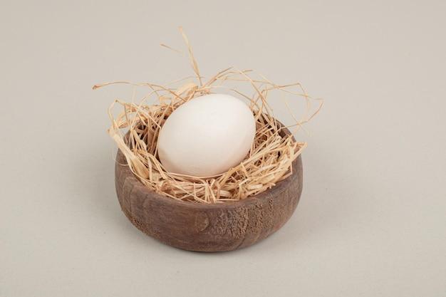 木製のボウルに干し草と新鮮な鶏の白い卵。