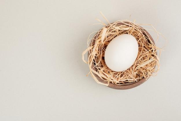 Свежее куриное белое яйцо с сеном в деревянной миске.