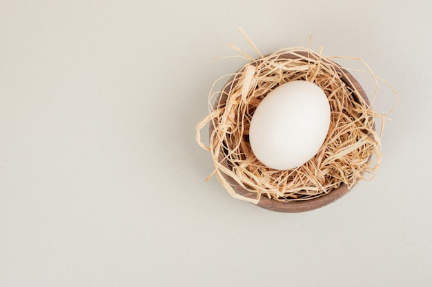 Fresh chicken white egg with hay in wooden bowl.
