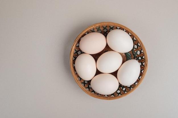 Uova bianche del pollo fresco sul canestro di vimini.