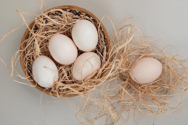 고리 버들 바구니에 건초와 신선한 닭고기 흰 계란.
