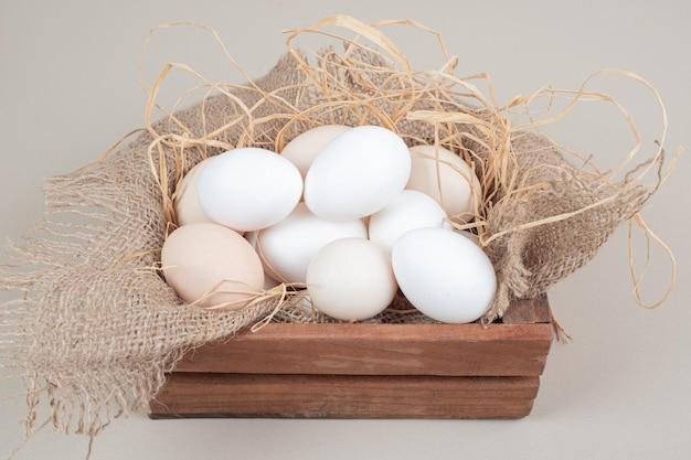 Свежие куриные белые яйца с сеном на деревянной корзине.