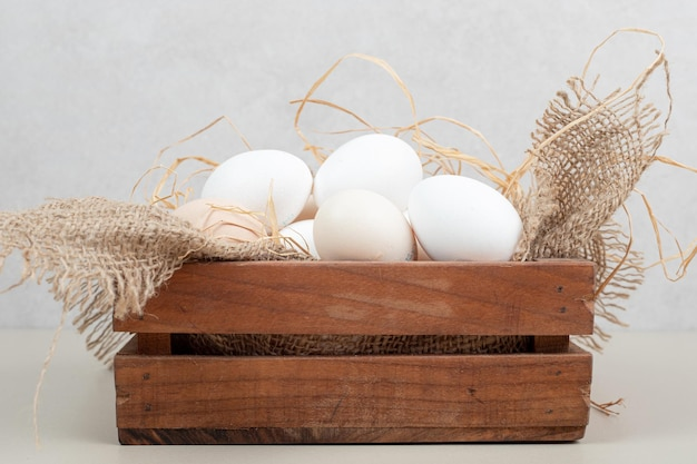Uova bianche del pollo fresco con fieno sul canestro di legno.
