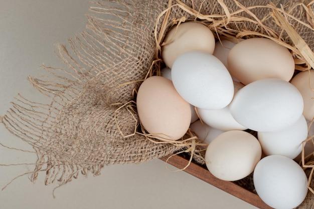 Fresh chicken white eggs with hay on wooden basket .