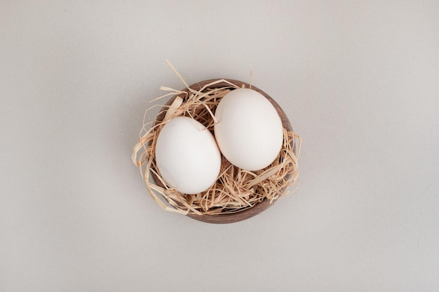 Fresh chicken white eggs with hay in wooden bowl.