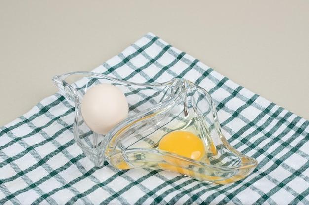 유리 접시에 노른자와 신선한 닭고기 흰 계란.
