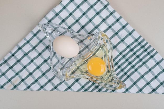 Свежие куриные белые яйца с желтком на стеклянной тарелке.