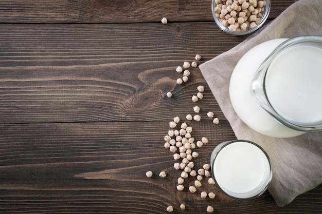 Fresh chickpea milk in glass and pitcher on dark wooden table background. rustic style.