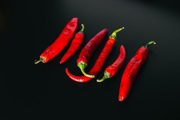 黒の背景に均等に配置された赤い色の新鮮な唐辛子。
