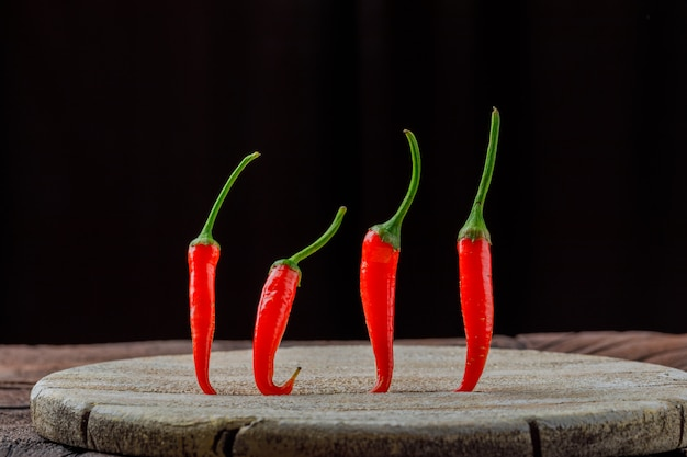 Fresh chili peppers on a wooden board side view on stone tile and black background